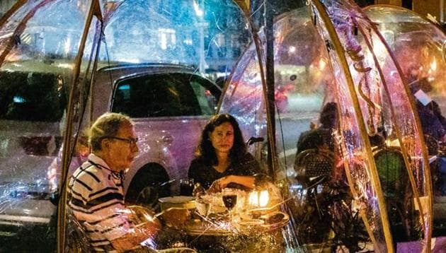 Customers dine in social distancing bubble tents at a restaurant in New York.(Bloomberg)