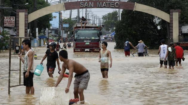 Residents negotiate a flooded road in Marikina, Philippines, on November 12. Residents posted images on social media of flooded homes and the disaster agency said parts of 36 cities and towns were inundated. (Aaron Favila / AP)