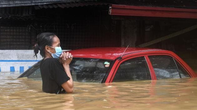 """A resident makes her way through a flooded street to shelter in Marikina City, suburban Manila on November 12. Roughly 40,000 homes had either been fully or partially submerged in the Marikina area, a situation its mayor, Marcelino Teodoro, said was """"overwhelming"""" and the worst since a typhoon flooded large swathes of the capital in 2009, Reuters reported. (Ted Aljibe / AFP)"""