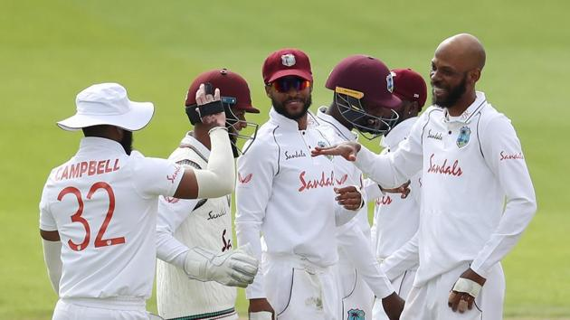 West Indies' Roston Chase celebrates taking the wicket of England's Rory Burns, caught by West Indies' Rakheem Cornwall with teammates.(REUTERS)