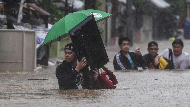 A man carries a television as residents make their way through a flooded street to shelter after Typhoon Vamco hit the area in Marikina City, suburban Manila on November 12. Nearly three million households in and around Manila were without power as people waded through waist-high floods, carrying valuables and pets, Reuters reported. (Ted Aljibe / AFP)