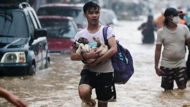 A man carries a dog, while evacuating from a flooded community in Marikina, Metro Manila, Philippines, on November 12. Typhoon Vamco struck areas still reeling from Goni, the most powerful typhoon in the world this year, which killed 25 people and destroyed thousands of homes earlier this month. (Eloisa Opez / REUTERS)