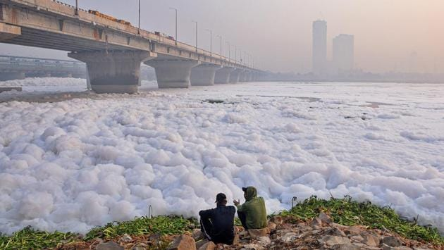 Men seen sitting along the banks of Yamuna river as a layer of toxic foam floats on its surface, at Kalindi Kunj in New Delhi on November 13. On average, 6,898 cases were reported each day during the last seven days, compared to 5,536 the week before, and 3,941 the week before that, HT reported. (Biplov Bhuyan / HT Photo)