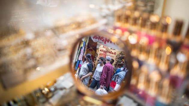 """Shoppers out on Dhanteras are reflected in a mirror, at Lajpat Nagar market in New Delhi on November 13. SAFAR's forecast added that even if residents do not burn any crackers –the capital in under a total ban on the sale and use any kind of firecrackers –the PM 2.5 level is still expected to be on the higher-end of """"very poor"""" or the lower-end of """"severe"""" category. (Prashanth Vishwanthan / Bloomberg)"""
