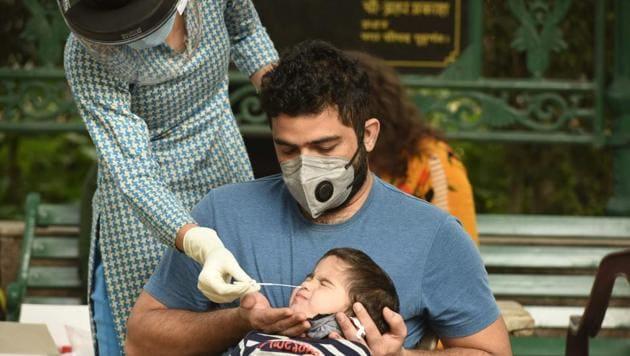 A health worker collects a swab sample from a child to test for coronavirus infection at Chhatrapati Shivaji Park in Shivaji Nagar, Gurugram on Thursday.(Parveen Kumar/HT Photo)
