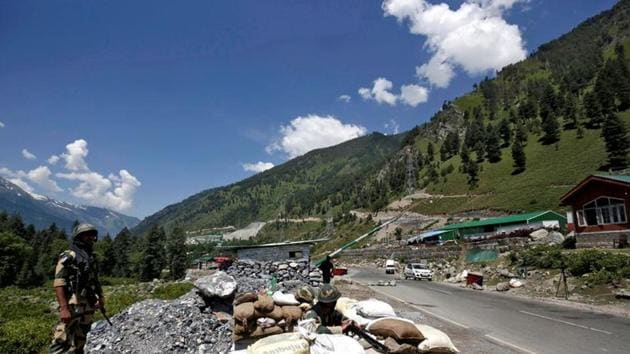 """India's Border Security Force (BSF) soldiers stand guard at a checkpoint along a highway leading to Ladakh. """"10-12 Pakistan Army soldiers injured in the Indian Army firing in which a large number of Pakistan Army bunkers, fuel dumps, and launch pads have also been destroyed,"""" officials said.(REUTERS)"""