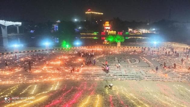 People light lamps made up of cowdung at the bank of Gomti River a day before Diwali, in Lucknow on Friday.(PTI Photo)