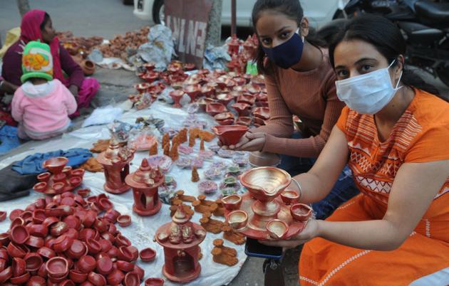 Young girls shopping for diyas at the Sector 19 market.(Keshav Singh/HT)