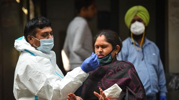 A healthcare worker in PPE coveralls collects a swab sample from a woman for coronavirus testing, in New Delh's Jahangirpuri on Friday.(Sanchit Khanna/HT Photo)