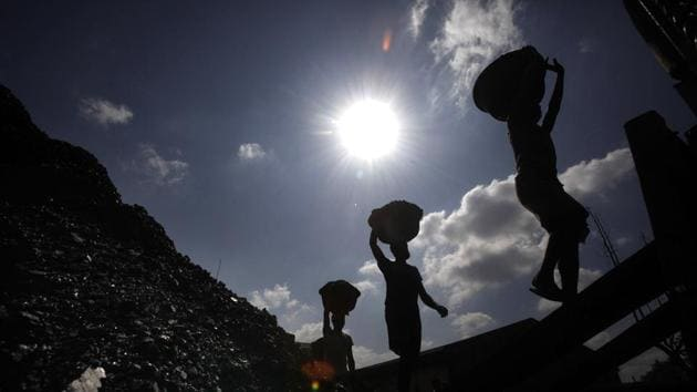 Laborers carry coal to load on a truck in Guwahati. The new rules state that no amendment will be required in the EC granted to the plant, even if the source of coal, and consequently, its distance from the thermal power plant changes.(AP)