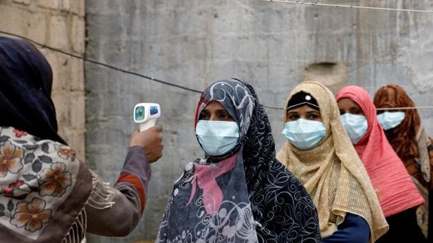Women wear protective masks as they get their temperature checked as the spread of the coronavirus disease (Covid-19) continues, in Karachi, Pakistan.(Reuters)