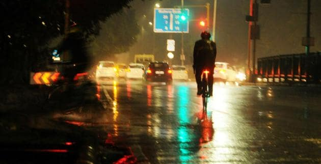 A cyclist caught in the showers that lashed Chandigarh on Sunday evening.(Keshav Singh/HT)