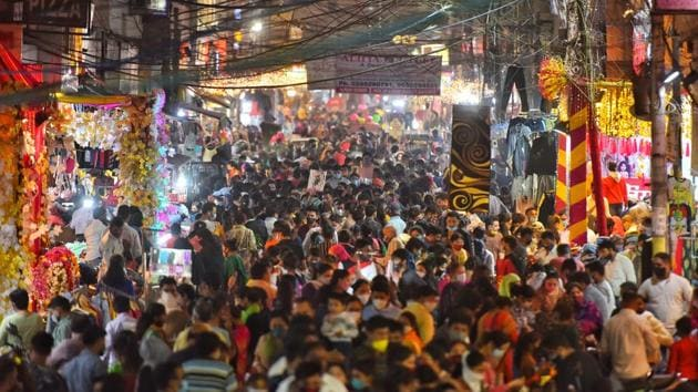People out shopping in large numbers on the eve of Diwali, at Kamla Nagar market in New Delhi on November 13. The markets were filled with holiday shoppers in the run-up to the festival but traders across cities told AFP that Covid-19 had scared them off spending amid the muted revelry. (Sanchit Khanna / HT Photo)