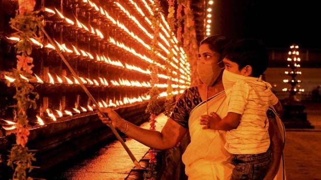 People light earthen lamp on the occasion of Diwali, in Thrippunithura on November 14. More than a billion Indians celebrated Diwali on Saturday amid twin concerns of a resurgence in coronavirus infections and rising air pollution that is enveloping the country's north in a cloud of thick toxic smog. (PTI)