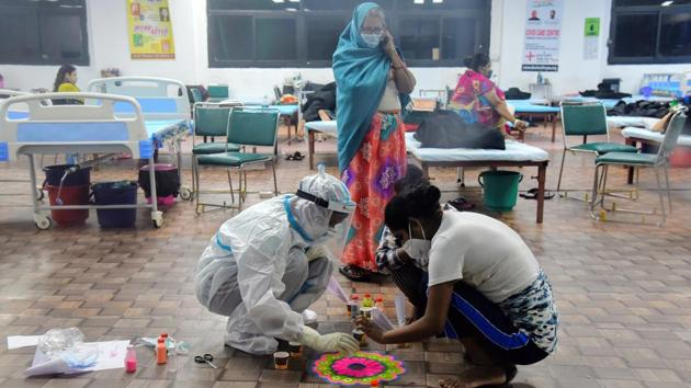A health worker in PPE and Covid-19 patients make rangoli on the occasion of Diwali festival, at CWG Covid centre in New Delhi on November 14. Diwali is meant to be the festival of light, but the pandemic has clouded the future for many in the country. (ANI)