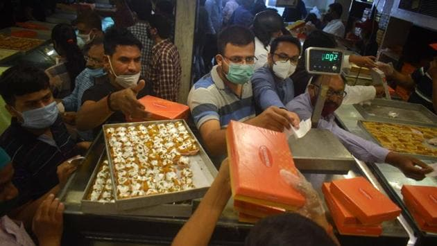People buy sweets at a shop on the occasion of the Diwali, in Prayagraj on November 14. The eight weeks up to Diwali can account for 40%of some traders' annual business, AFP reported and is also considered an auspicious time to buy gold. (PTI)