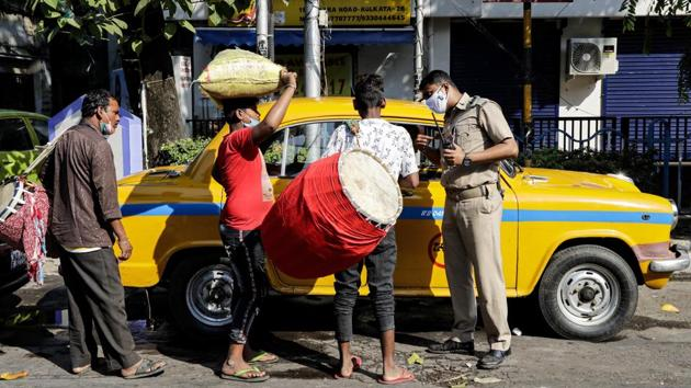 A policeman helps traditional drummers, who had travelled from villages, hire a taxi to be dropped at a worship venue for a performance, in Kolkata on November 14. On the twin occasions of Diwali and Kali Puja celebrations across several states, many temples across the country streamed prayer sessions online to avoid large gatherings. (Bikas Das / AP)