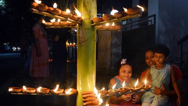 A woman and children light earthen lamps on the occasion of Diwali, in Guwahati on November 14. The looming pandemic saw people cut down on typical celebrations that involve socializing and exchanging gifts with friends and family; lighting oil lamps or candles in private ceremonies instead. (ANI)
