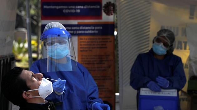 A healthcare worker wearing personal protective equipment (PPE) takes a swab sample from a man to be tested for the coronavirus disease (Covid-19) in Mexico City, Mexico.(Reuters)