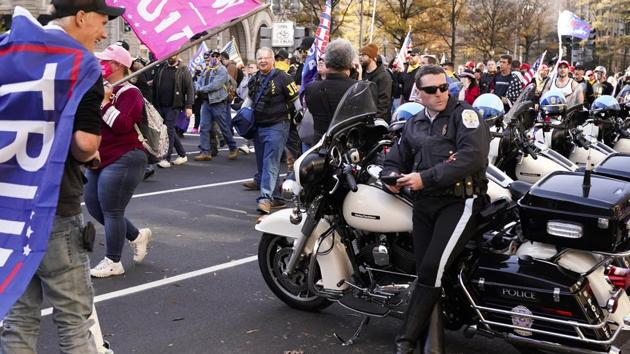 """A police officer sits by his vehicle people dressed in clothing with """"Proud Boys"""" on it march down Pennsylvania Avenue on November 14 in Washington D.C. The marchers included members of the Proud Boys, a neo-fascist group known for street brawling with ideological opponents at political rallies, AP reported. (Jacquelyn Martin / AP)"""