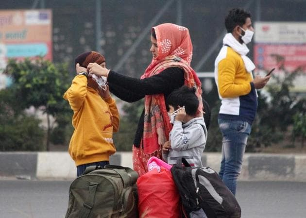 A family gears up for the cold near Rajiv Chowk in Gurugram on Monday. The temperature has fallen in Delhi and the national capital region (NCR) due to rain.(PTI Photo)