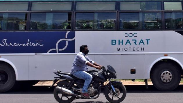 A man rides his motorcycle past a parked bus of Indian biotechnology company Bharat Biotech outside its office in Hyderabad.(REUTERS)