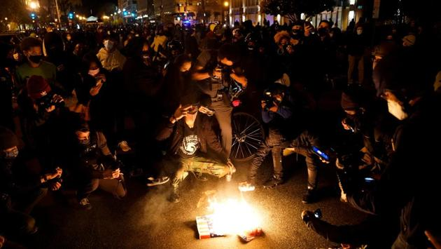 """Protesters set fire to a Make America Great Again (MAGA) hat and a poster depicting US President Donald Trump in Washington on November 14. Trump seemed to be following the evening's events, taking to Twitter to accuse the city's mayor of """"not doing her job"""" and calling on the police to """"get going - do your job and don't hold back,"""" AFP reported. (Erin Scott / REUTERS)"""