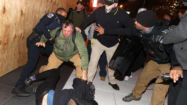 """A police officer tries to break up a fight between Black Lives Matter protesters and members of the Proud Boys during a protest following the """"Million MAGA March"""" on November 14, in Washington D.C. (Tasos Katopodis / Getty Images / AFP)"""