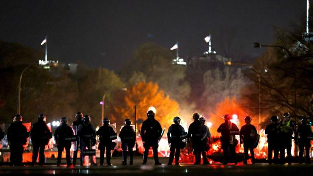 """Police officers stand in line as they monitor a protest following the """"Million MAGA March"""" from Freedom Plaza to the Supreme Court, on November 14. As night fell, multiple police lines kept the two sides apart. (Tasos Katopodis / Getty Images / AFP)"""