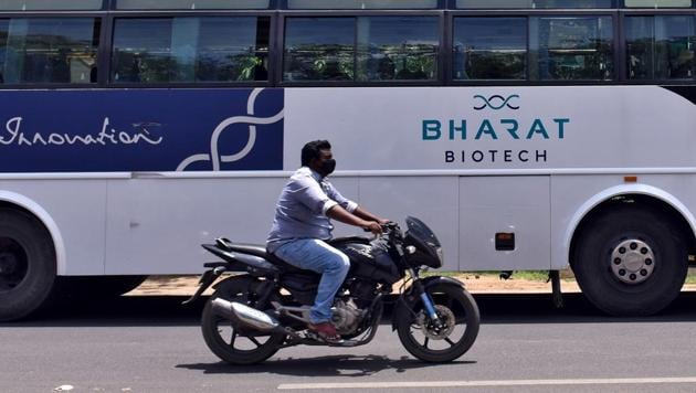 FILE PHOTO: A man rides his motorcycle past a parked bus of Bharat Biotech outside its office in Hyderabad (REUTERS/Stringer/File Photo)