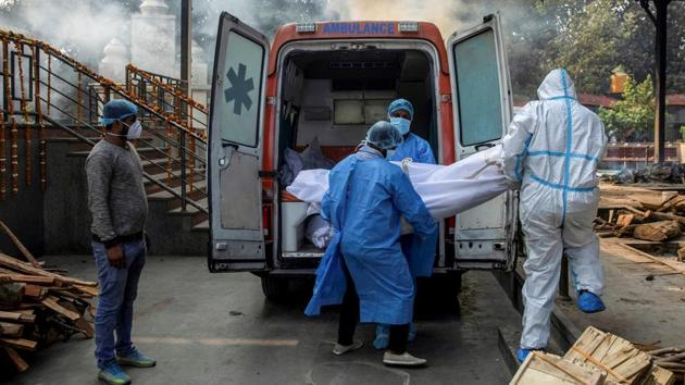 Health workers and a relative carry the body of a Covid-19 victim from an ambulance to a crematorium in New Delhi on November 13. Delhi currently has 40,128 active Covid-19 cases. The city has seen 4,41,361 recoveries and 7,713 deaths, as per the Ministry of Health and Family Welfare (MoHFW) on November 17. (Danish Siddiqui / REUTERS)