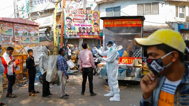 A health care worker collects a swab sample from a man at a mobile coronavirus testing kiosk, as others queue at a wholesale market, in New Delhi on November 17. In the grip of an unprecedented wave of infections, the Union government has announced reinforcement of health infrastructure and human resources in Delhi to tackle what has been described as possibly the worst outbreak of Covid-19 anywhere in the country yet. (Adnan Abidi / REUTERS)