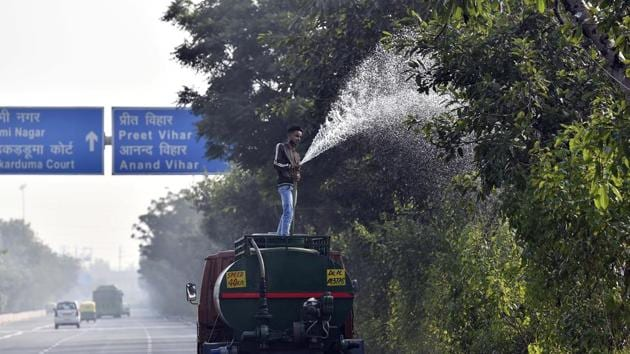 A Public Works Department (PWD) worker sprays water on trees as a pollution control measure, at Vikas Marg near ITO Bridge in New Delhi on November 17. According to the Ministry of Earth Sciences' System of Air Quality and Weather Forecasting And Research (SAFAR), stubble burning accounted for eight per cent of Delhi's PM2.5 pollution on November 18. It was three per cent a day prior. (Sanjeev Verma / HT Photo)