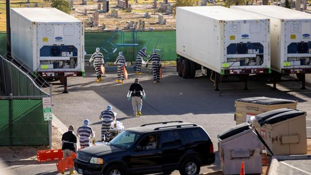 El Paso County detention inmates help move bodies to refrigerated trailers outside the Medical Examiner's Office which is located next to a cemetery in El Paso on November 16. In the border city of El Paso, overwhelmed morgues have begun paying jail inmates $2 an hour to help transport the bodies of Covid-19 victims. (Ivan Pierre Aguirre / REUTERS)