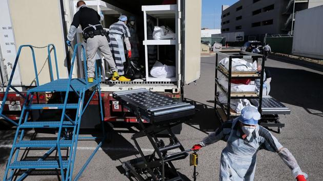 Low-level inmates load bodies of Covid-19 victims into a refrigerated morgue trailer in El Paso on November 16. Over the past two weeks, the rolling average number of daily new cases has increased by 3,430.4 --an increase of 53.6%. (Mario Tama / Getty Images / AFP)
