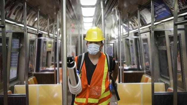 A contractor uses an electrostatic sprayer to disinfect subway cars to control the spread of Covid-19, in New York.(AP File Photo)
