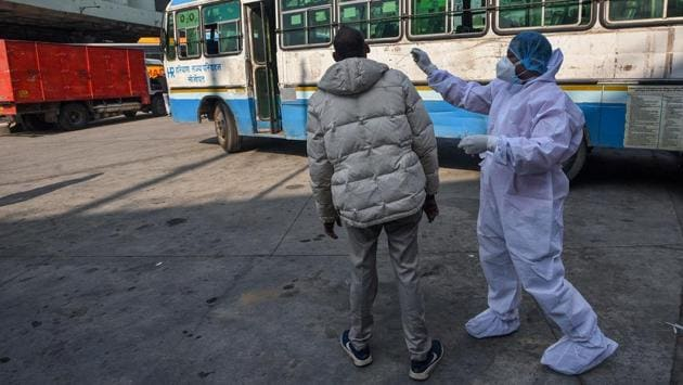 A health worker collects a swab sample from a passenger to test for Covid-19 near Kashmere Gate Inter State Bus Terminal (ISBT) in New Delhi on November 22. In its third and the most severe Covid-19 wave yet, Delhi has continuously reported cases above 5,000-mark since October 28. This surge reached its highest on November 11 when single-day cases breached 8,000 mark. (Biplov Bhuyan / HT Photo)
