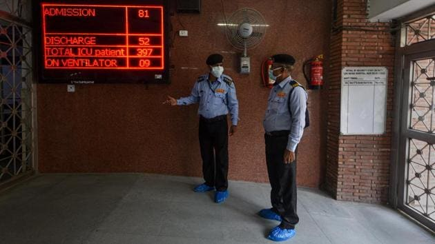 Security guards in conversation near a Covid-19 bulletin board at Lok Nayak Jai Prakash (LNJP) Hospital in New Delhi on November 18. The state government's Delhi Corona App also showed that 55 per cent of hospital beds earmarked for coronavirus patient were occupied on November 21, while 86.8 per cent intensive care unit (ICU) beds are being used to give care to patients with a severe level of infection, HT reported. (Biplov Bhuyan / HT Photo)