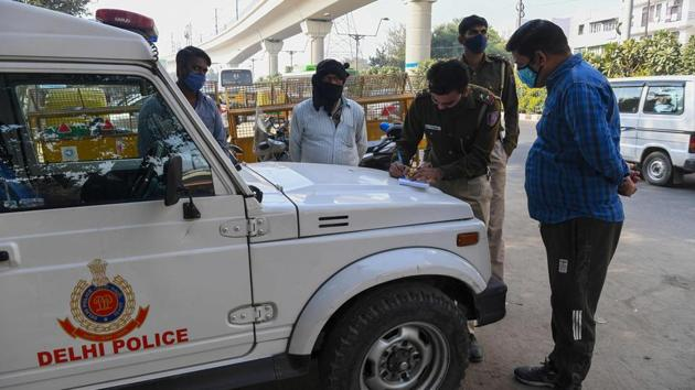 A policeman fines a commuter for not maintaining social distancing as a preventive measure against coronavirus infection in New Delhi on November 22. Meanwhile, the penalty for not wearing a mask in public has also been increased from ₹ 500 to ₹ 2000 in the light of a worsening third-wave of coronavirus infections. (Prakash Singh / AFP)
