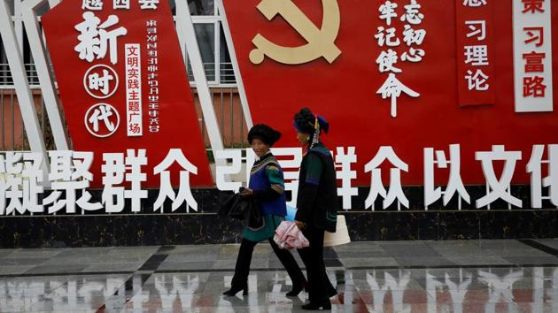 Ethnic Yi women walk past an installation featuring a logo of Communist Party of China at the Chengbei Ganen Community, a residential complex built for a relocation programme as part of China's poverty alleviation effort, in Yuexi county.(Reuters file)