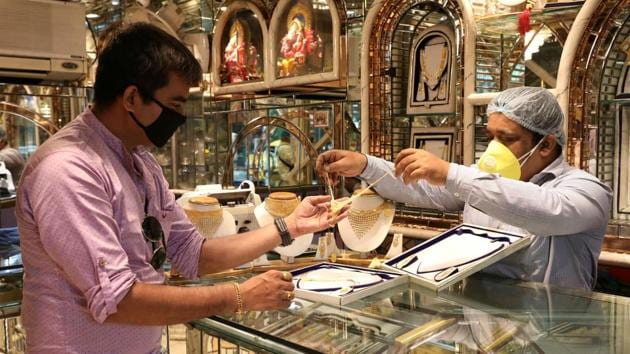 A salesman shows gold necklaces to a customer at a jewellery showroom in Kolkata.(Reuters Photo)