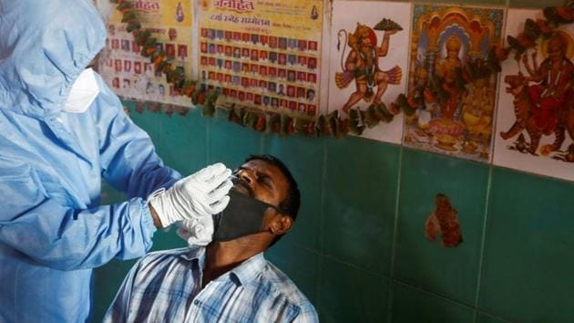 A health worker in personal protective equipment (PPE) collects a swab sample from a man during a rapid antigen testing campaign for the coronavirus disease (Covid-19) at a vegetable market in Mumbai.(Reuters)