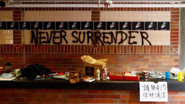 "The slogan ""Never Surrender"" is spray painted on a wall in the besieged Hong Kong Polytechnic University (PolyU) in Hong Kong, China.(Reuters)"