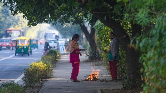 Women warm themselves next to a fire at RK Puram in New Delhi on November 22. After the Western Disturbance passes, cold winds will again start blowing from the region and the mercury is set to dip again from November 27, HT reported. (Amal KS / HT Photo)