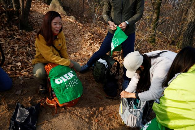Kim Kang-Eun gets ready with her colleagues to collect litter while hiking a mountain in Incheon, South Korea, November 16, 2020. (REUTERS)