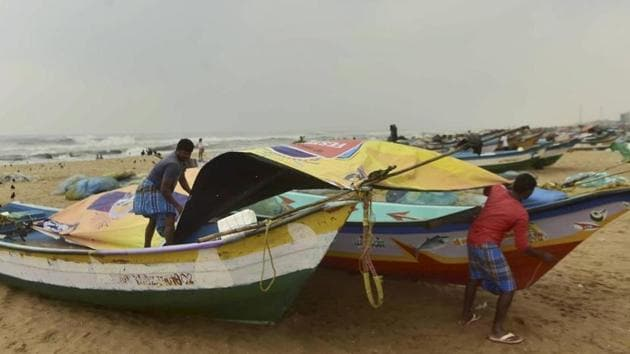 Fishermen cover their boats at Marina Beach during heavy rain, triggered by Cyclone Nivar, in Chennai on Tuesday.(PTI PHOTO.)