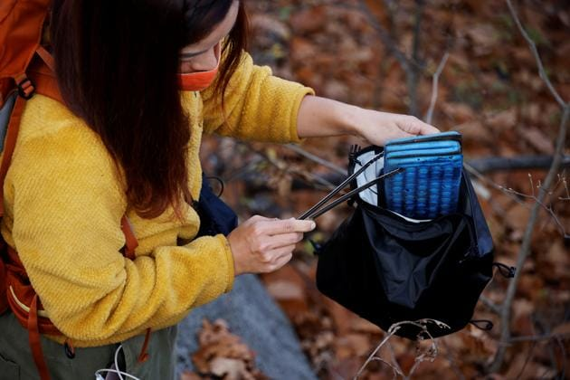 Kim Kang-Eun collects a litter while hiking a mountain in Incheon, South Korea, November 16, 2020. (REUTERS)