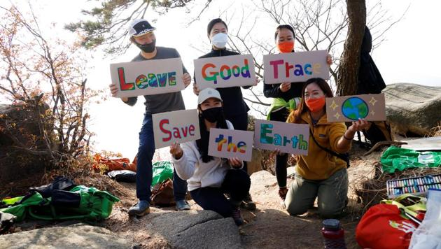Kim Kang-Eun, an artist who leads Clean Hikers, and her colleagues pose with signs bearing a message for hikers on a mountain in Incheon, South Korea, November 16, 2020. Picture taken November 16, 2020. (REUTERS)