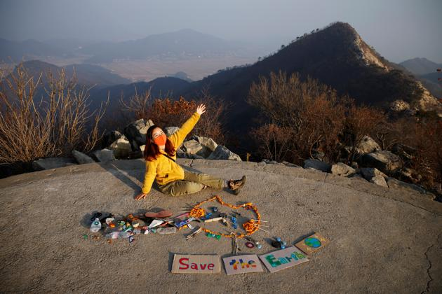 Kim Kang-Eun poses artwork made from litter collected by members of Clean Hikers during their hikes, on the peak of a mountain in Incheon, South Korea, November 16, 2020. (REUTERS)