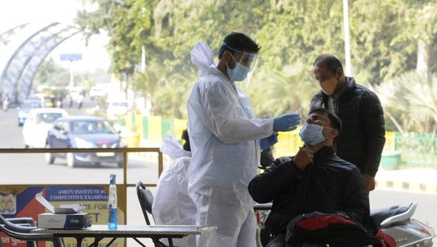 Noida, India - November 23, 2020: A medical worker in PPE collects a sample from a commuter arriving from Delhi to test for coronavirus infection, at Sector 14A Uttar Pradesh-Delhi border, in Noida, India, on Monday, November 23, 2020. (Photo by Sunil Ghosh / Hindustan Times)